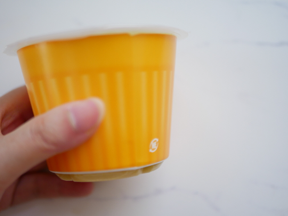 野菜をMotto!!の黄色いカップとそれを持つ左手