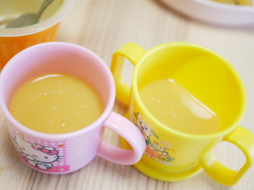 一杯の野菜をMotto!!コーンスープを子供用のプラスチックカップ2つに等分している