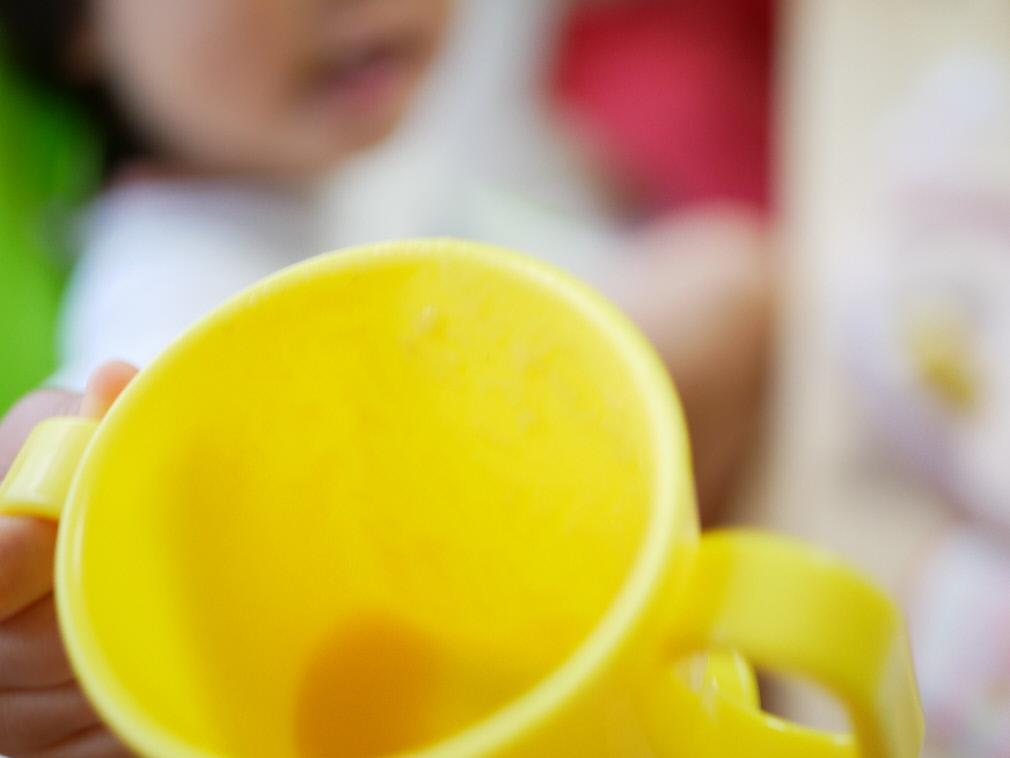 野菜をMotto!!を飲み干して空になった子供用プラスチックカップを見せる赤ちゃん
